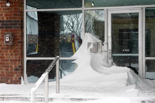 一家公司門口,被風雕塑而成的奇形雪堆